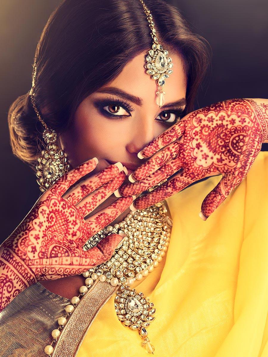 Indiase vrouw draagt gele sari met Indiase sieraden en heeft henna